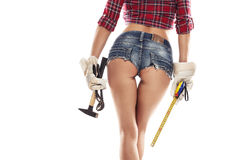 Nice woman mechanic showing buttock and holding hamme. R pliers and measuring tape isolated over white background royalty free stock photography