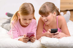 Nice sisters lying on settee Royalty Free Stock Images