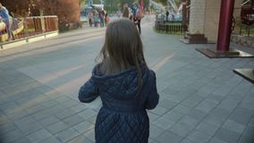Pretty girl walks in a children park in autumn in slow motion stock footage