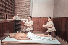 Nice skilled masseuses preparing for the massage. Almost ready. Nice skilled masseuse putting massage oil while preparing for the massage stock photos