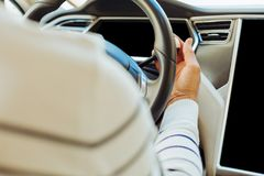 Nice skillful man holding a steering wheel. Moving forward. Close up of a nice pleasant skillful man holding a steering wheel while driving the car Stock Photography