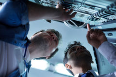 Nice skillful technicians looking at the network server. Problem detection. Nice skillful male technicians looking at the network server and detecting problems royalty free stock photos