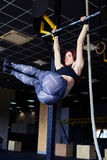 Nice slender woman exercising on the horizontal bar. Low angle of nice slender woman exercising on the horizontal bar. Sport, fitness, lifestyle and people Stock Photo
