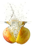 Nice sliced apple falling into water. Ripe sliced apple falling into water, splashes all around Stock Photography