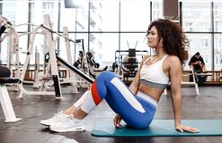 Nice slim curly dark-haired girl dressed in sports clothes is sitting on the mat for fitness in the modern gym with a royalty free stock image