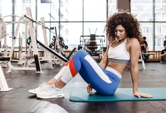 Nice slim curly dark-haired girl dressed in sports clothes is sitting on the mat for fitness in the modern gym with a royalty free stock photo