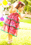 Nice small girl dancing outdoors. Little female child enjoying her 3-year old birthday party, colorful balloons decoration, sweet cheerful kid having fun Stock Photo