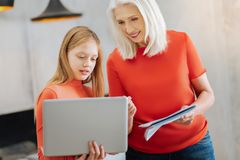 Nice smart girl holding a laptop. School project. Nice smart pleasant girl holding a laptop and talking to her grandmother while preparing a school project Stock Photo