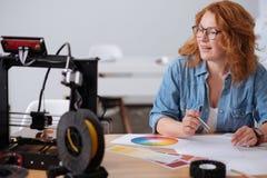 Nice smart kvinna som ser skrivaren 3D Royaltyfri Fotografi