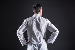 Nice smart scientist wearing a labcoat. Modern laboratory. Nice smart professional scientist standing in the lab and wearing a labcoat while thinking about his Royalty Free Stock Photography