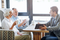 NIce smiling aged couple having meeting in the cafe. Ensure your future. Positive delighted loving aged couple sitting at the table and having a meeting with Royalty Free Stock Photos