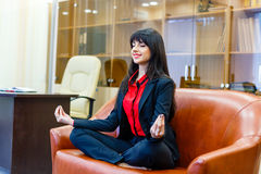 Nice smiling businesswoman sitting on sofa in the lotus positi Stock Photography