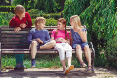 Nice smiling children sitting on the bench Royalty Free Stock Image