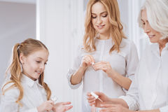 Nice smiling female family members using nail polish Stock Image