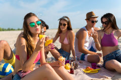 Nice smiling friends having a picnic. Positive emotions. Cheerful attractive women sitting on the blanket and blowing soap bubbles while having a picnic with her Royalty Free Stock Photography