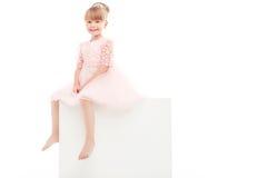 Nice smiling girl sitting on white box Royalty Free Stock Photography