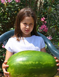 Nice smiling little girl with an enormous WATERMELON Stock Photos