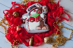 Nice snowman with deer glazed on Christmas gingerbread laying among red decorations, beads, nuts on wooden table Royalty Free Stock Photo
