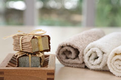 Nice soaps with towels in natural colours. Soaps,towels amd wook basket with a blurred background Royalty Free Stock Images