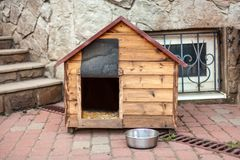 Nice solid wooden doghouse without a dog settled close to the house, with an empty bowl. Outdoors, summer time. Copy space royalty free stock photography