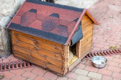 Nice solid wooden doghouse without a dog settled close to the house. With an empty bowl, outdoors, summer time. Red roof. Copy space stock image