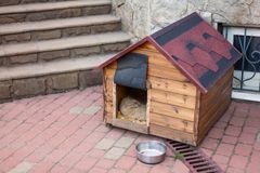 Nice solid wooden doghouse without a dog settled close to the house. With an empty bowl, outdoors, summer time. Red roof. Copy space royalty free stock photo