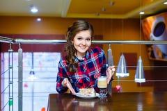 Nice som ler flickasammanträde i ett kafé med en kopp av mokachino och Royaltyfri Foto