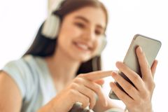 Pleasant teenage girl scrolling her music playlist. Nice songs. The focus being on the phone in the hands of a charming teenage girl looking through her playlist Royalty Free Stock Images