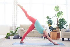 Nice sportswoman being in one-legged downward-facing dog asana Royalty Free Stock Images