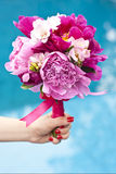 Nice spring flower bouquet. A nice wedding bouquet of purple, pink and white peonies held by a bride Royalty Free Stock Photos
