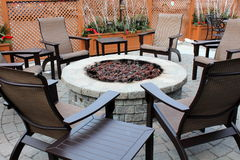 Nice stone fireplace with outdoor chairs. Stock Photos
