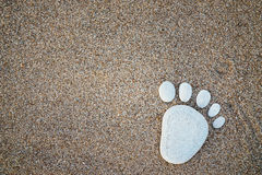 Nice stone made footprint on the sand shore, background. Stock Photos