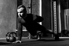 Nice strong man developing his muscles. Strong and athletic. Nice persistent young man doing push ups and holding one hand behind his back while developing his stock photos