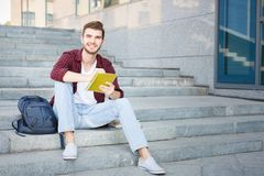 Nice student sitting on the stairs and writing notes outdoors. Nice student sitting on the stairs and writing notes to his notebook, preparing for exams, smiling Royalty Free Stock Photos