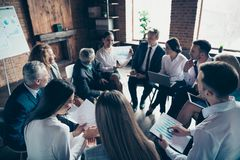 Nice stylish cheerful experts professional ceo boss chief sitting on chairs in circle showing financial plan result. Corporate conference at modern industrial royalty free stock photo