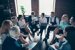 Nice stylish elegant classy top sharks sitting on chairs in circle discussing finance plan data global organization. Conference at modern industrial loft royalty free stock photography