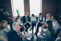 Nice stylish elegant top sharks sitting on chairs in circle discussing plan growth global organization at modern. Industrial loft interior work place space royalty free stock image
