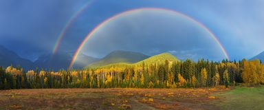 Nice summer rainbow over the mountains. Amazing rainy and cloudy day. Canadian Rocky Mountains, Canada. stock image