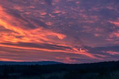 Nice sunset clouds in blue hour with hills stock photography