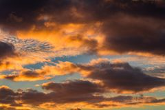 Nice sunset orange cumulus clouds on blue sky.  stock photo