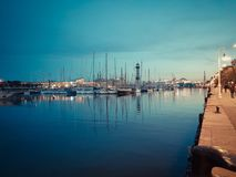 BARCELONA, SPAIN - March 27, 2017: Port Vell embankment panoramic view. Pedestrian walking on the promenade and admiring the yacht. Nice sunset over the harbour stock image