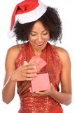 Nice surprise from Mrs Claus. Attractive ethnic female in Santa hat excited by surprise Christmas present in pink gift box Stock Images