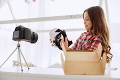 Cheerful girl examining VR headset while recording vlog. Nice surprise. Pleasant beautiful pre-teen girl examining a VR headset having taken it out of a parcel Stock Photos