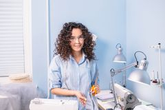 Nice tailor with wavy hair looking at camera in workshop. Style. fashion. working day Royalty Free Stock Photo