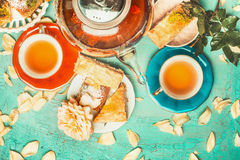 Nice tea brunch scene with colorful cup of tea, tea pot , cakes and flowers on turquoise shabby chic background. Top view Royalty Free Stock Photography