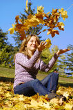 A nice teen girl plays with golden leaves Stock Photos