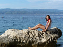 Nice teenage girl posing on the rock on the beach in Croatia. Croatian beach in the summer day with a beautiful young woman Royalty Free Stock Photography