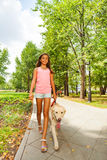 Nice teenage girl walk her dog in park alley Stock Photos