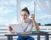 Nice teenager teen girl student is sitting at the table with boo royalty free stock photography