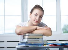 Nice teenager teen girl student is sitting at the table with boo royalty free stock photos